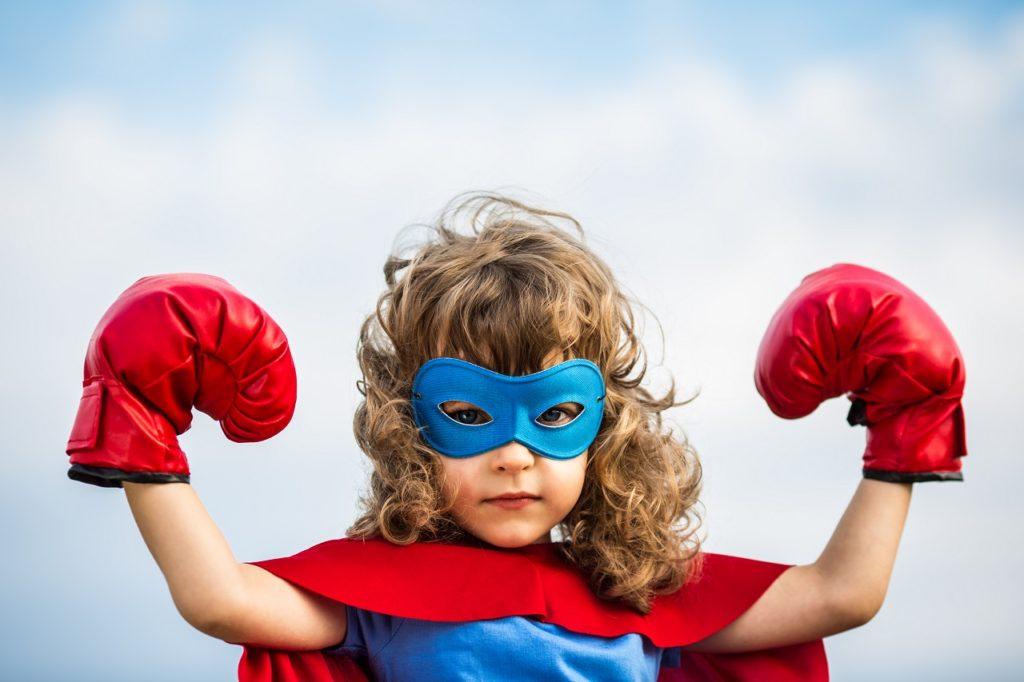 Superhero kid wearing boxing gloves against blue sky background.